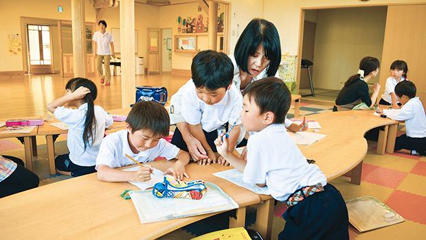 ぬくもりある木造の部屋で宿題をする子どもたち