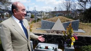上栗頼登さんの反原爆の叫びが刻まれている原爆犠牲者の慰霊碑の前で説明する、長男で現園長の上栗哲男さん