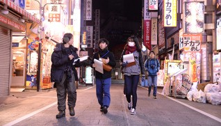 深夜の新宿で調査する学生たち