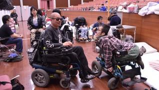 障害者らのために講堂が開放された。中央は日隈さん(4月19日午後5時)