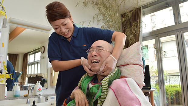 介護職員からつぼマッサージを受ける安田さん