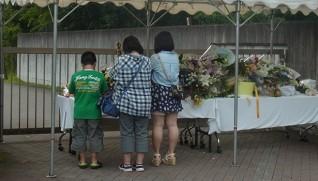 津久井やまゆり園の献花台で手を合わせる親子(1日)