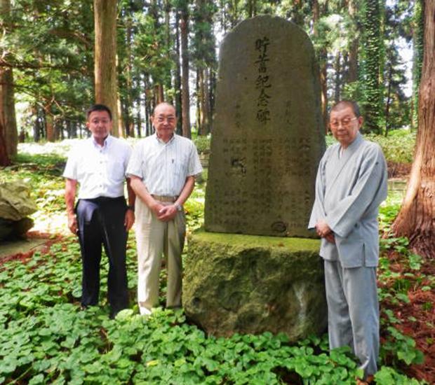 記念碑を前に、右から宮原文彌理事長、兜森和夫理事・事務局長、小林儀貴事務局次長