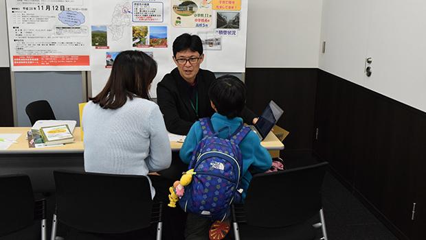 長野県須坂市の職員(奥)から説明を聞く親子