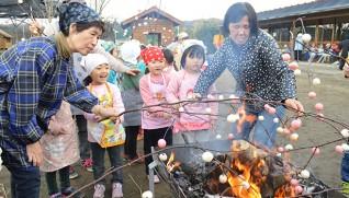 熱さに耐えながらも楽しそうに団子を焼く園児たち